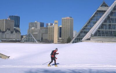 Cross country skiers in Edmonton's river valley in front of the Muttart Conservatory
